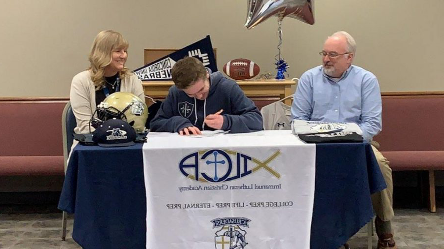 Liam getting really excited for his next opportunity while signing the papers.  He is accompanied with his mom Cindy (right) and dad Vince (left).